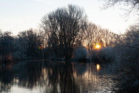 The frozen world in the early morning during colorful sunrise near a river in winter