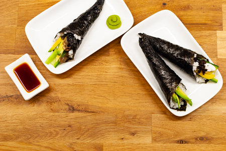 Top view Side view of homemade vegan Temaki-Sushi filled with avocado on a small plate on a wooden table with soy sauce and wasabi