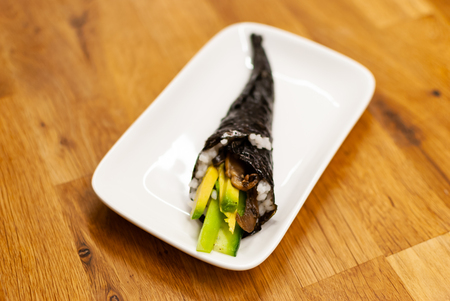 Side view Side view of homemade vegan Temaki-Sushi filled with avocado on a small plate on a wooden table Фото со стока
