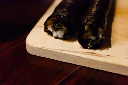 Close up of two sushi rolls on a wooden plate on a wooden table