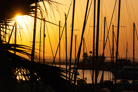 Silhouettes of Sail boats in the ocean, the blue sky and the golden sun during sunset in the background - back light Stock Photo