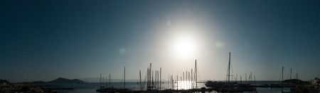 Silhouettes of sail boats in the ocean, the blue sky and the sun in the background - back light Stock Photo