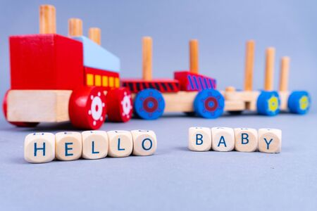 Letters in the front saying Hello Baby, a colorful wooden train in the back - newborn concept 版權商用圖片