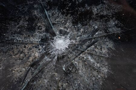 Cracks in a window glass coming from a bullet - close up