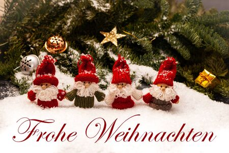 """Christmas dwarfs standing on snow, green twigs in the back with christmas ornaments, the German words """"Frohe Weihnachten"""" for merry christmas in front"""