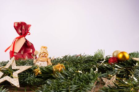 Christmas ornaments (snow man, present, stars, baubles) and fir twigs in front of a white background
