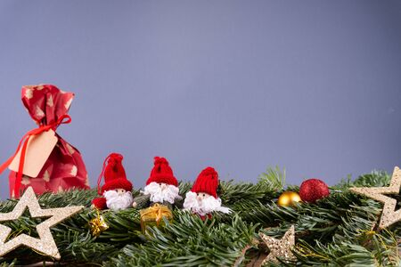 Christmas ornaments (dwarfs, present, stars, baubles) and fir twigs in front of a gray background