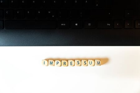 """Wooden cubes with the German word """"Impressum"""" for imprint legal notice together with a black keyboard on white backgr - top view"""