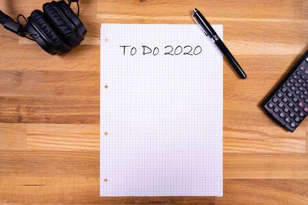 """Een notitieblok met een notitie """"To Do 2020"""" samen met een pen, een rekenmachine en een koptelefoon op een houten tafel"""