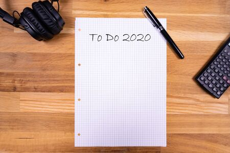 """Notatnik z karteczką """"To Do 2020"""" wraz z długopisem, kalkulatorem i słuchawkami na drewnianym stole"""