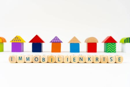 """Wooden block with letters saying """"Immobilienkrise"""" (German for real estate crisis) in front of colorful toy houses Standard-Bild"""