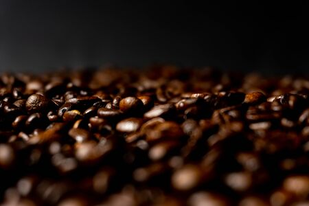 Close up of fresh roasted brown coffee beans - angled view with copy space