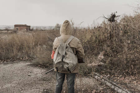 wandering boy. boy with a gun. boy goes to an abandoned building. boy stands in front of a building. Post apocalypse. man traveling on foot in a post-apocalyptic world in search of food Stock Photo