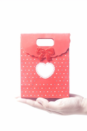 Hand holding red gift bag, isolated on the white background photo
