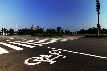 crosswalk: zebra crossing and bicycle sign forming abstract design on the street