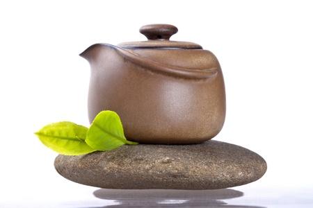 ollas de barro: La tetera y la hoja fresca en piedra con el fondo blanco Foto de archivo