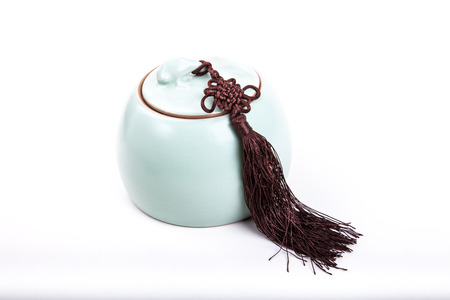 Vintage or antique light green tea canister with tassel isolated on white background photo