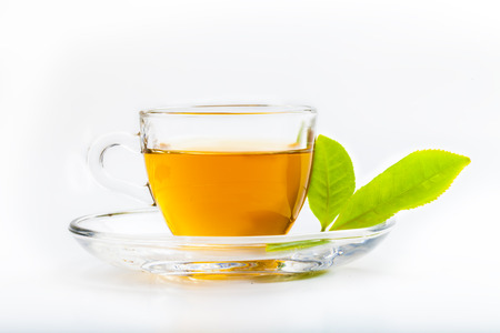 Green tea leaf and glass cup of black tea isolated on white background photo