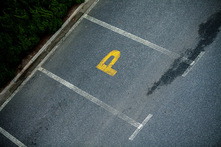 Look down empty parking spot with vegetation and shrubbery  from above photo