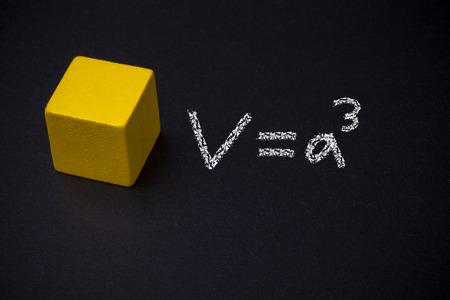 schoolroom: Cube and mathematical formulas on blackboard Stock Photo