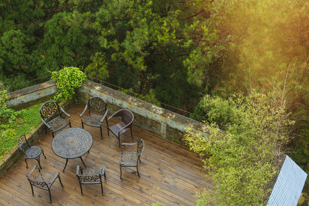look down: Wooden deck surrounded by trees with seating arrangement with steel metal framed table and chairs by look down. Stock Photo