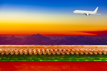 Airplane in sky at sunrise over red walls, meaning China and East Asia airline travel