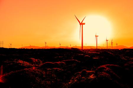 Wind turbines at orange sunrise.