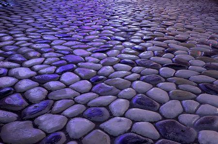 Pebbles on the ground under the neon light irradiation Stock Photo