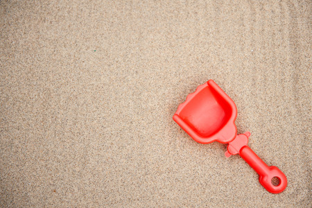 Gray toy shovel stuck in pile of beach sand. Stock Photo