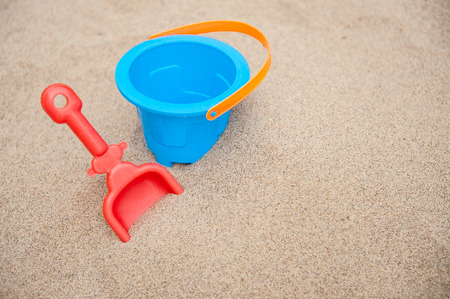 Plastic bucket and spade on a sandy beach. Stock Photo