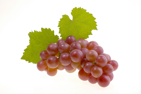 Bunch of ripe red grapes with leaves isolated on white background Stock Photo