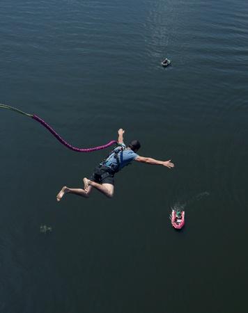 bungee jumping: el hombre con el seguro volar hasta el agua, abri� sus brazos, el barco en hacia abajo Foto de archivo