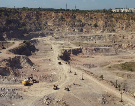 backhoe and dump trucks in large quarry mining of granite,  photo
