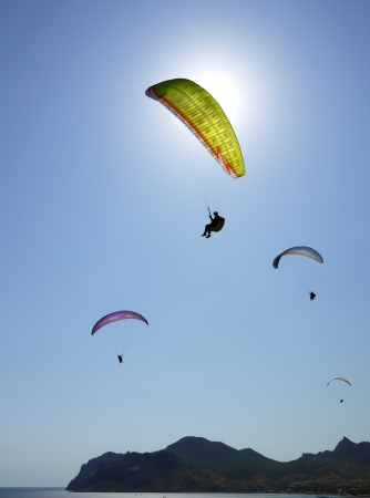 slings: few paragliders in the blue sky above the sea