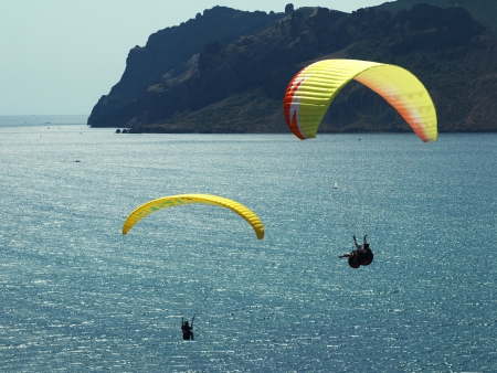paragliding in the blue sky above the sea and rocks