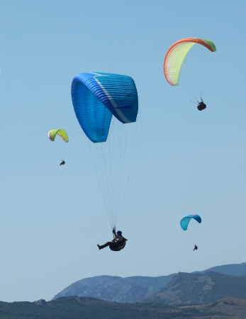paragliding: few paragliders in the blue sky above the rocks Editorial