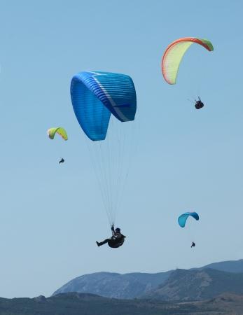 parapendio: parapendio pochi nel cielo blu sopra le rocce