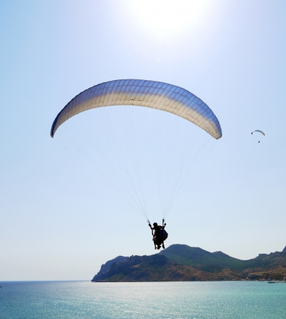 sensations:  paraglider in sky above the sea, on a background of rock Stock Photo