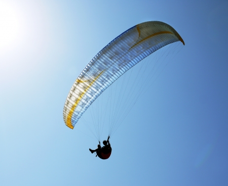 silhouette of paraglider against the clear blue sky
