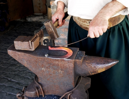 horseshoe on an anvil in the forge and the hands of a blacksmith at work photo