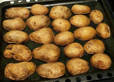 oven potatoes: baked  in the oven potatoes on a baking tray