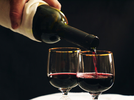 is poured into wine glass red wine, dark background