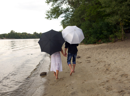 tryst: the guy and the girl are under umbrellas on the river bank Stock Photo