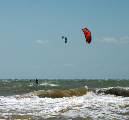 twain athletes with a paraglider on the sea waves