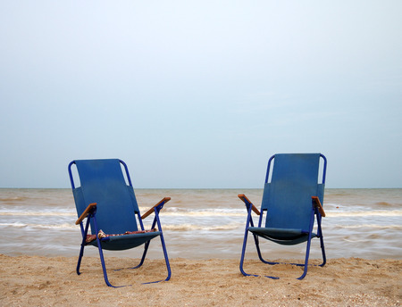 eventide: two blue beach chairs on the beach near the sea, eventide