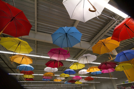 disclosed: many multicolored umbrellas hanging under the ceiling of a trading hall Stock Photo