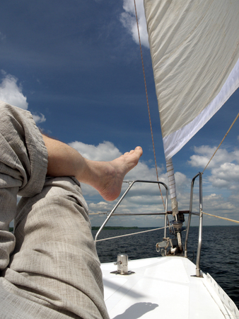 bare foot: bare foot of a man who is lying on the deck of the yacht, blue sky, white clouds and sail