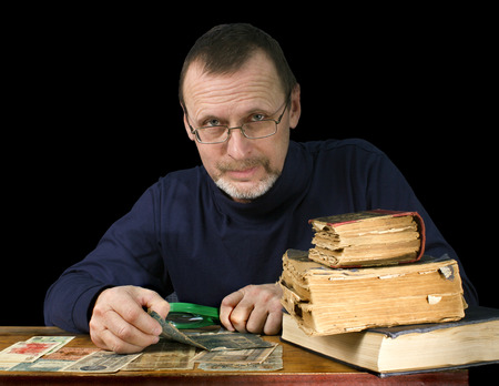 numismatist: portrait of an elderly man with old books and bank notes