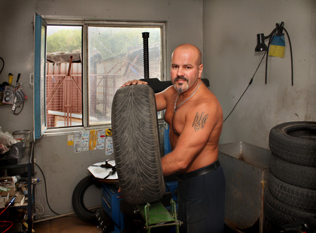 mounter: man mounter of tires with a tattoo Emblem of Ukraine Stock Photo
