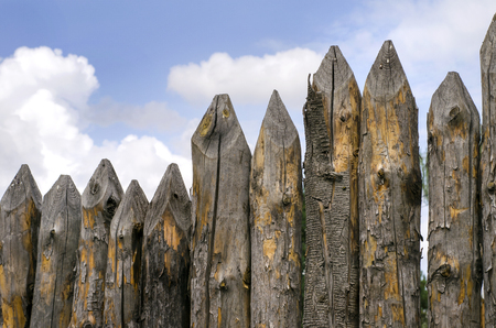 pointed stockade, a fence made of pine logs against the sky Stock Photo